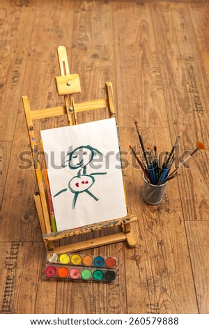 easel with children painting with colors and brushes at art school - stock photo