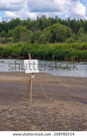 Easel with empty canvas on the bank of the river