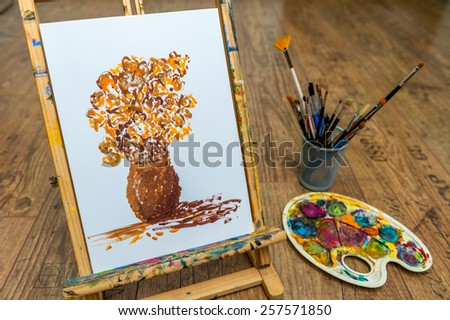 easel with flower student drawing with paint for art school - stock photo
