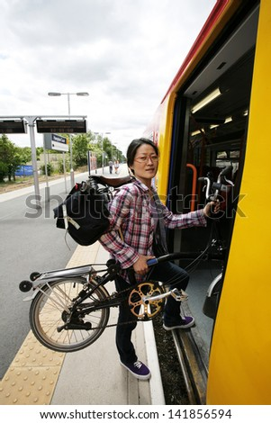 East Asian Woman carrying a folding bike getting on a train.   - stock photo