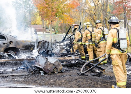 EAST CHINA, MI, USA / NOVEMBER 5, 2013: Firefighters respond to a garage fire in East China, MI on November 5, 2013. The garage and the contents, including 3 vehicles and a boat were a total loss.