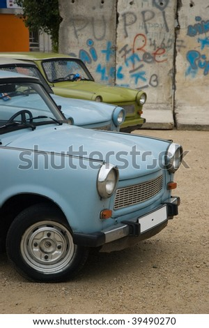 East-German plastic vintage cars parked near Berlin wall - stock photo