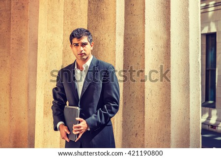 East Indian American Businessman traveling, working in New York. Wearing black suit, holding laptop computer, college student standing by columns on campus, looking forward. Instagram filtered effect. - stock photo