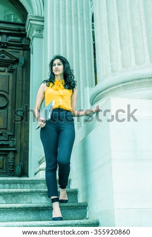 East Indian American college student studying in New York, wearing sleeveless orange shirt, striped pants, high heels, carrying laptop computer, walking down stairs. Filtered look with cyan tint.  - stock photo