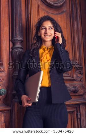 East Indian American woman working in New York, wearing black blazer, orange undershirt, standing by vintage office doorway, arm carrying laptop computer, talking on cell phone. Instagram effect.  - stock photo