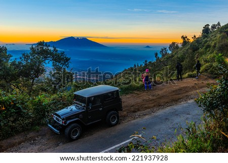 EAST JAVA,INDONESIA-JUNE 05 : Tourists with Jeep at Mount Penanjakan. The best views from Mount Bromo and the surrounding volcanoes are at sunrise on June 05,2014 in East Java , Indonesia. - stock photo