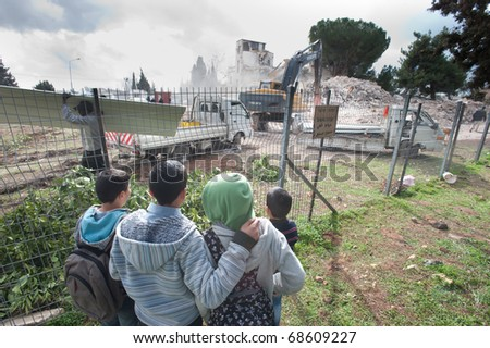 EAST JERUSALEM - JANUARY 9: Palestinian children watch as Israeli contractors demolish the Shepherd Hotel in Sheikh Jarrah to make way for new Jewish settlements in East Jerusalem on Jan 9, 2011 in East Jerusalem.