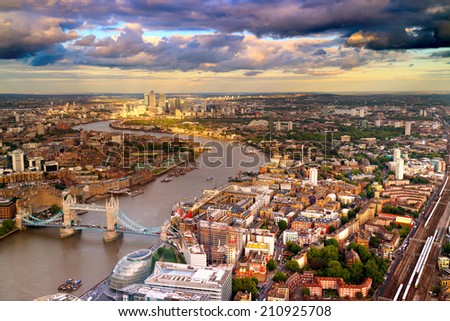 East London Skyline showing Tower Bridge,  Canary Wharf, City Hall and the Thames River. Taken during a cloudy sunset. - stock photo