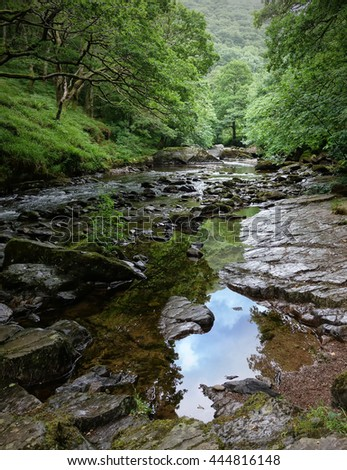 East Lyn River, Lynmouth, Exmoor, Devon, England. Large rocks and reflections in the water.           - stock photo