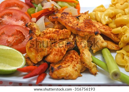 East meet West, hot chicken paprika with fresh steamed vegetables and macaroni and cheese