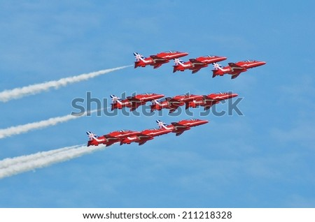 EASTBOURNE, ENGLAND - AUGUST 14, 2014: RAF aerobatic team The Red Arrows perform at the annual free Airbourne airshow. Formed in 1965, the team are celebrating their 50th display season. - stock photo