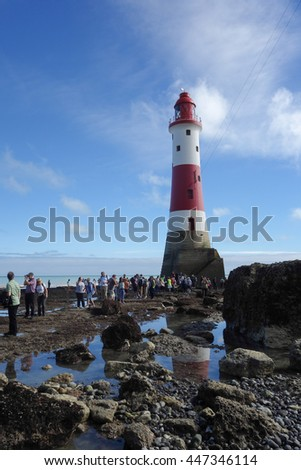 EASTBOURNE, ENGLAND - JULY 3. People walk to Beachy Head Lighthouse during low tide on July 3, 2016, Eastbourne, East Sussex, England, selective focus