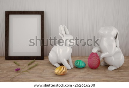 Easter abstract composition with easter bunnies, eggs, and frame in front of a white wall  - stock photo