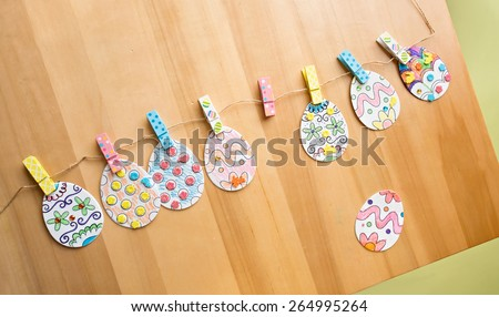 Easter activities and crafts project: colorful easter eggs decorated with pencils and markers and stickers, made into a banner - stock photo