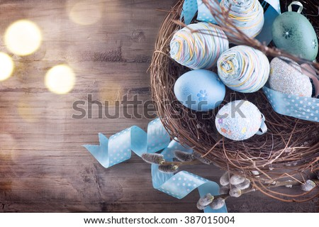 Easter background. Beautiful colorful eggs with spring flowers over wooden brown background border design - stock photo
