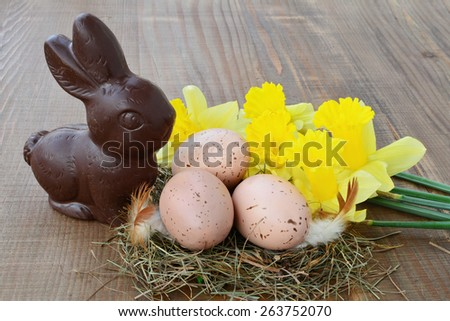 Easter background, chocolate bunny, spotted eggs in nest, daffodils on wooden background. - stock photo