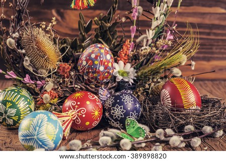 Easter background. colored Easter eggs in the nest and composition of dried flowers and plants. on wooden background. easter theme. happy easter - stock photo