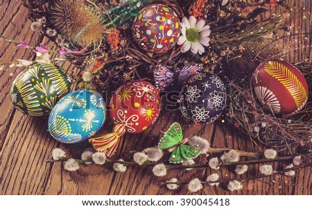Easter background. colored Easter eggs in the nest and composition of dried flowers and plants. on wooden background. easter theme. happy easter.instagram toning effect. light effect - stock photo