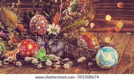 Easter background. colored Easter eggs in the nest and composition of dried flowers and plants. on wooden background. easter theme. happy easter. instagram toning effect - stock photo
