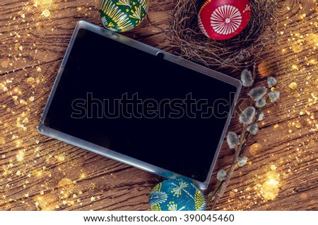 Easter background. colored Easter eggs in the nest. Blooming willow and a tablet pc on the wooden background. Easter themed. Happy Easter. Instagram toning effect - stock photo