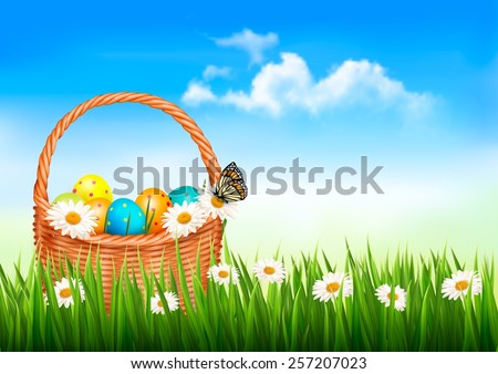Easter background. Easter eggs and flowers in a basket in the grass.