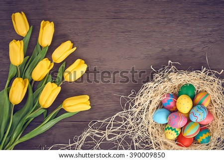Easter background, eggs, rabbit, yellow tulips. Hand painted decorated eggs, happy bunny handmade, spring flowers on wood, copy space.  Still life, top view.Unusual creative holiday greeting card  - stock photo