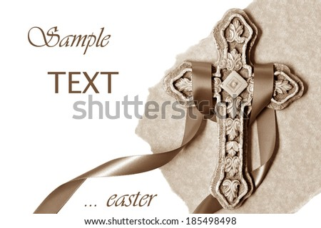 Easter background image of small ornate stone cross with satin ribbon and parchment paper.  Sepia tones on white background with copy space.  - stock photo
