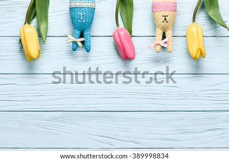 Easter background, rabbits, pink yellow tulips. Happy bunny handmade and spring flowers on blue wood, copy space. Still life, top view. Unusual creative greeting card  - stock photo
