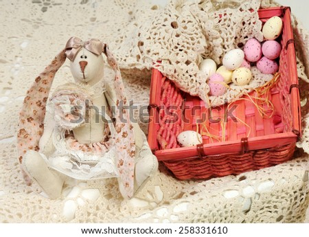 easter background with a handmade linen rabbit with long floral pink ears and bright basket with beige and pastel pink candy eggs on hand knitted lace tablecloth - stock photo