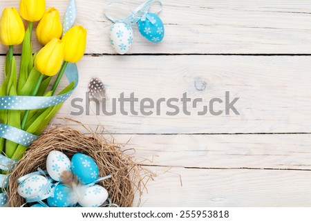 Easter background with blue and white eggs in nest and yellow tulips. Top view with copy space - stock photo