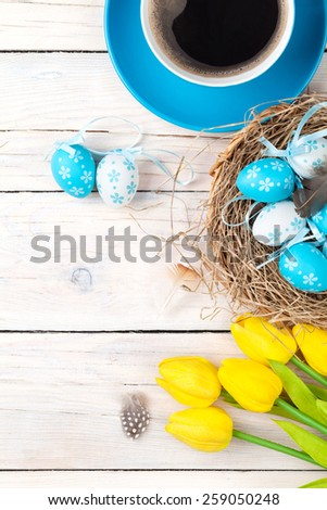 Easter background with blue and white eggs in nest, yellow tulips and coffee cup over white wood. Top view with copy space - stock photo