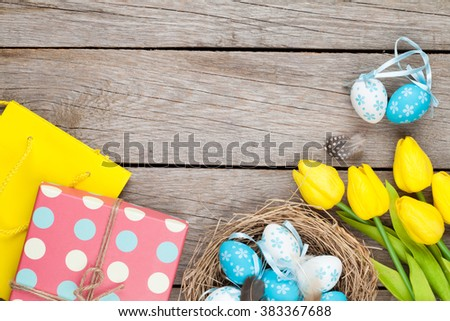Easter background with blue and white eggs in nest, yellow tulips and gift box. Top view with copy space - stock photo