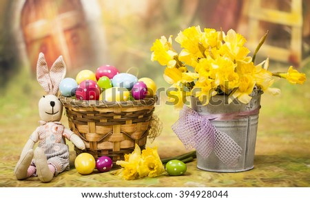 Easter background with colorful Easter eggs and a bouquet of yellow daffodils
