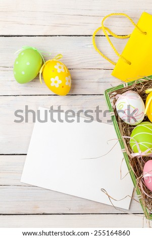Easter background with colorful eggs, yellow tulips and greeting card over white wood. Top view with copy space - stock photo