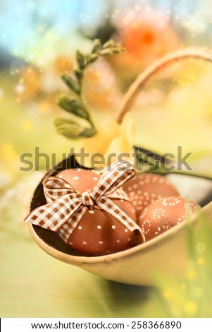 Easter background with eggs and spring flowers, shallow DOF, focus on the bow and part of front egg. This image is toned.  - stock photo