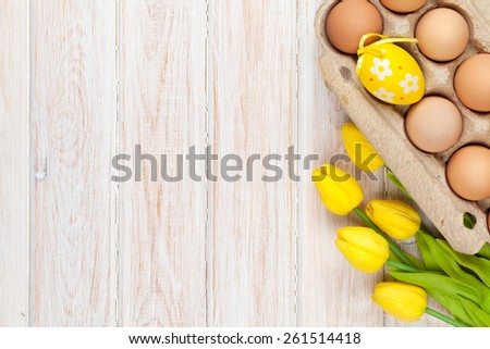 Easter background with eggs and yellow tulips over white wood. Top view with copy space - stock photo