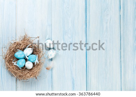 Easter background with eggs in nest over wood. Top view with copy space - stock photo