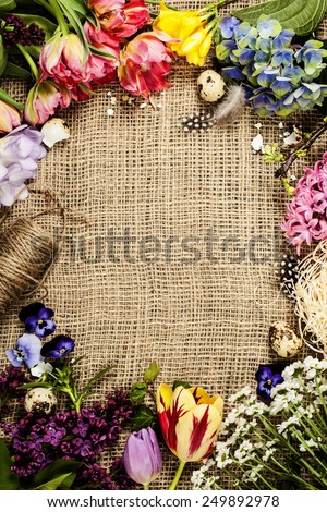 Easter background with eggs, nest and flowers - stock photo