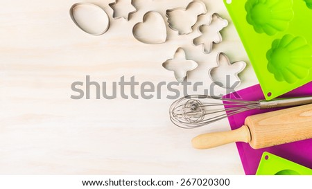 Easter bake tools with cookie cutter, cake mould for muffin and cupcake  on white wooden background, top view, place for text - stock photo