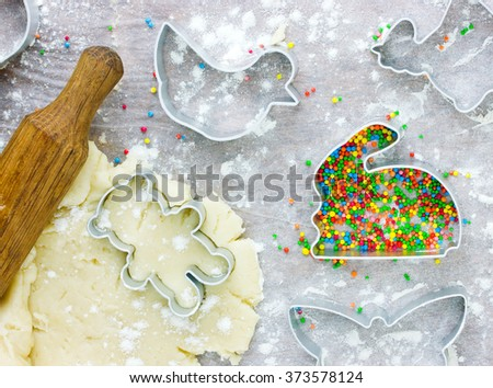 Easter baking raw dough and bunny cutter for holiday cookies on a white table. Top view - stock photo