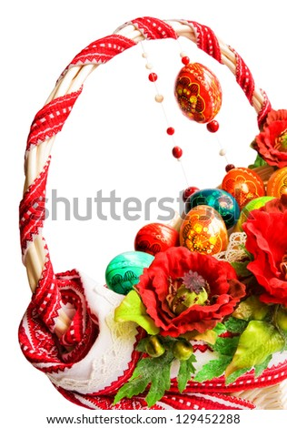 Easter basket decorated with embroidery, poppies and colorful eggs isolated on white - stock photo