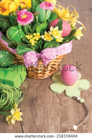 Easter basket on wooden table with handmade decorations, space for your greeting text