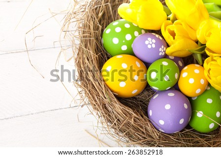 Easter basket with colored eggs over wooden background - stock photo