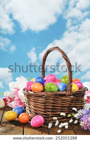 Easter basket with colored hen�s eggs, tulip, hyacinth and pussy willow in front on wooden board - stock photo
