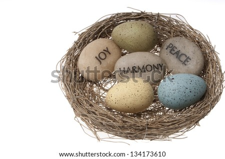 Easter basket with coloured speckled eggs and message stones isolated on white background