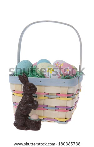 Easter basket with dyed colorful eggs and rabbit on white background