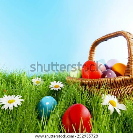 Easter basket with eggs on green meadow with flowers