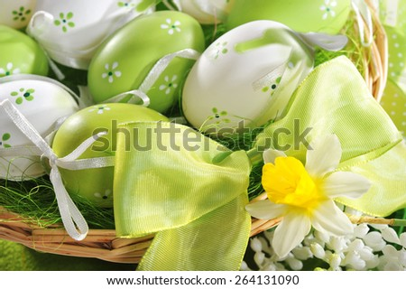 easter basket with many colored easter eggs, green bow and narcissus - stock photo
