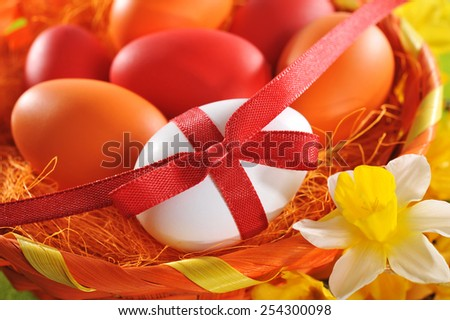 easter basket with many colored easter eggs, red bow and narcissus - stock photo