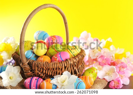 Easter basket with many painted easter eggs, narcissus - stock photo